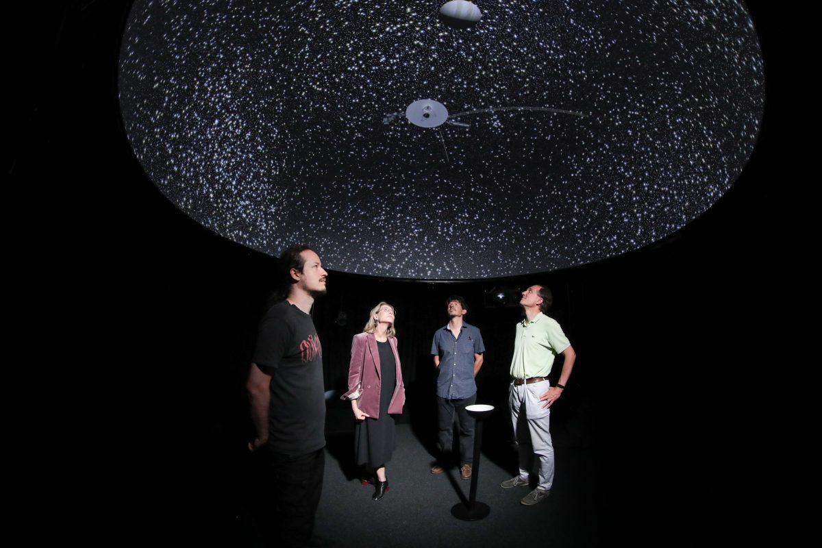 (De gauche à droite:) Florian Cabot, Sarah Kenderdine, Yves Revaz et Jean-Paul Kneib, sous une projection de l'univers virtuel dans un dôme.  Photo credit: Alain Herzog / EPFL.